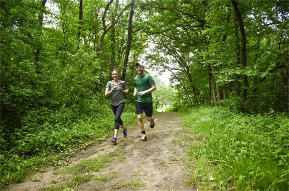 A couple runs through Lake Elmo Park Reserve in the new green spring foliage.