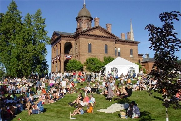 People sitting on the lawn of the Washington County Historic Courthouse at an ice cream social