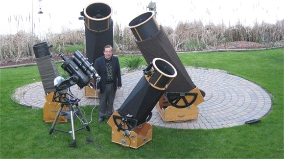 Mike Lynch stands with a number of his telescopes.