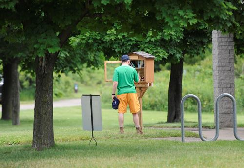 A man checks out the books in a Little Library in Washington County Parks