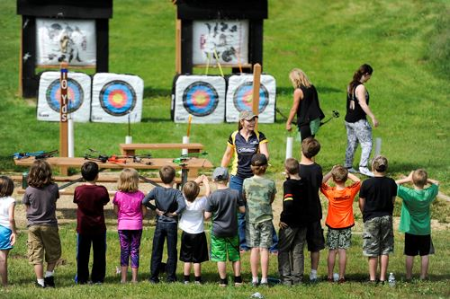 A group of children who are in an archery class line up before their instructors and targets