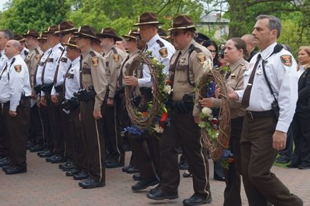 deputy sheriffs and correctional officers carrying circles of flowers to the steps of the old courth