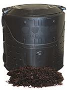 Black home compost bin cylinder with brown dirt in front of big