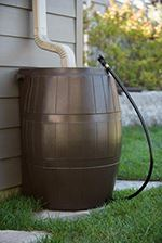 Brown rain barrel next to house with siding connected to a rain gutter with hose attached to rain ba