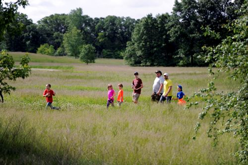 A group of children and adults hike across a grassy field at Lake Elmo Park Reserve
