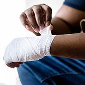 Man wrapping hand with gauze Opens in new window
