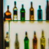 Bottles of liquor on a shelf with green hue and back light Opens in new window